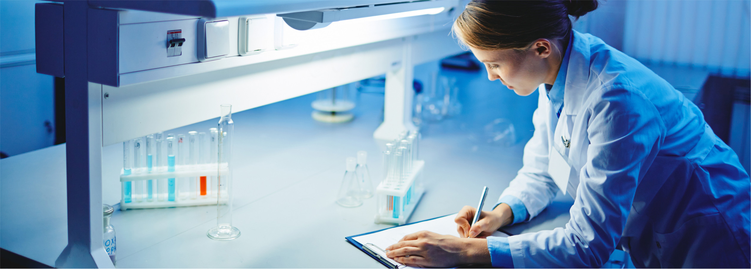 Female researcher making notes in laboratory